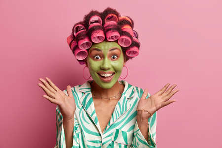 Excited cheerful woman spreads palms and giggles positively gets nice advice from beautician how to care about skin applies beauty mask and hair rollers prepares for first date wants to look beautiful