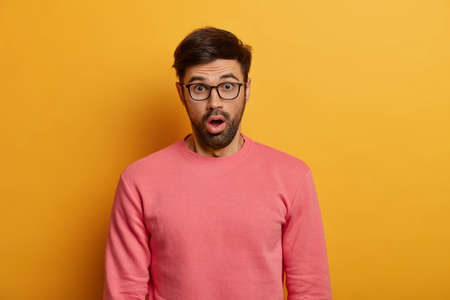 Startled young unshaven man gasps hearing stunning news, sees unbelievable price fall, expresses excitement and astonishment, wears pink sweater, has eyes popped out, isolated on yellow studio wall