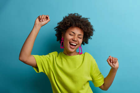 I am winner. Ecstatic overjoyed African American woman dances carefree, celebrates victory and success, dressed in green casual t shirt, feels lively and energetic, isolated on blue background Stock fotó