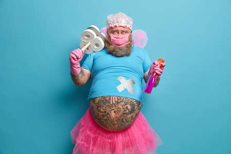 Bearded fairy of purity does cleaning in house, holds necessary detergent, sanitizes everything to fight coronavirus, wears protective mask, isolated on blue background, busy with domestic chores