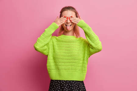 Playful girlfriend covers eyes and stricks out tongue, has fun and foolishes around, plays with her younger sister, dressed in loose knitted green jumper, poses against rosy studio wall, feels crazy