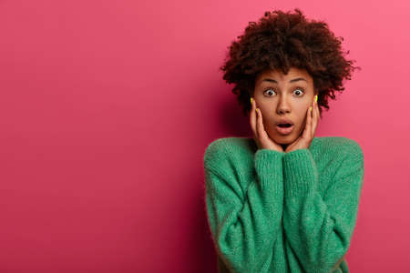 Photo of shocked stunned Afro American woman hears fresh rumor, has eyes popped out, opens mouth from wonder, hears gossip, cannot believe in shocking thing happened recently, wears green sweater
