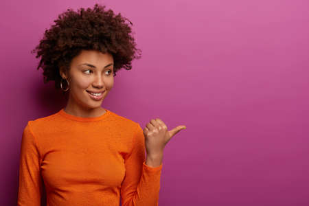 Cheerful Afro American woman shows chart or product, indicates thumb at empty space against purple background, suggests check out advertisement, shows awesome promo offer or special discount