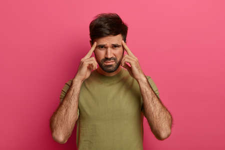 Depressed frustrated bearded man frowns and keeps index fingers on temples, cannot focus, thinks up idea, ponders on decision, feels headache or migraine, wears casual t shirt poses on pink wall Banque d'images