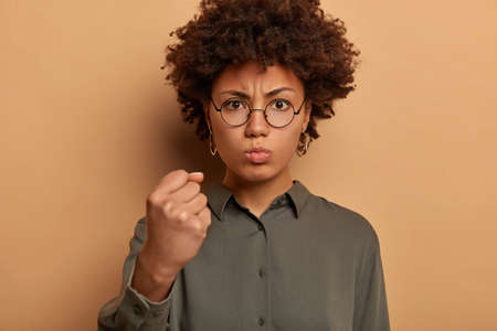 Outraged angry woman shows clenched fist to camera, has strict facial expression, needs respect, demands good behaviour, expresses anger and irritation, threatens to revenge, wears stylish shirt Banque d'images