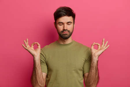 Relieved bearded young man relaxes during meditation, keeps eyes closed, spreads palms sideways in nirvana, wears casual t shirt, practices yoga, inhales fresh air, isolated on pink studio wall