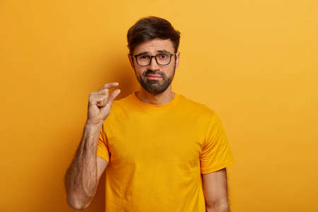 Bearded man makes hand gesture, advice to have small amount of something, purses lips, suggests spend some time together, dressed in yellow t shirt and eyewear, poses indoor. Size and measuring