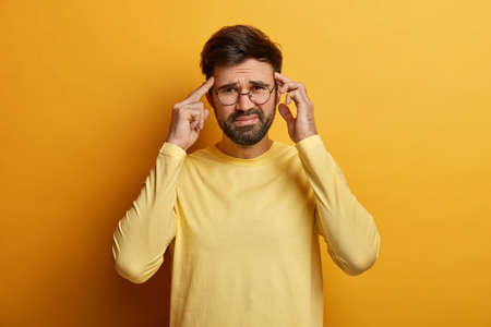 Dissatisfied man thinks intensely, touches temples with index fingers, smirks face, suffers from unbearable headache, wears casual sweater, poses indoor feels pressure and distress, isolated on yellow