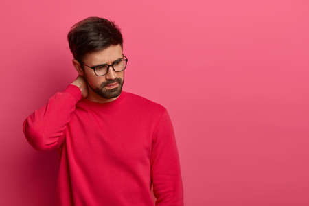 Thoughtful troublesome young man in eyewear concentrated down, keeps hand on neck, thinks deeply about something, contemplates and makes serious decision, has thick beard, models over rosy background Banco de Imagens
