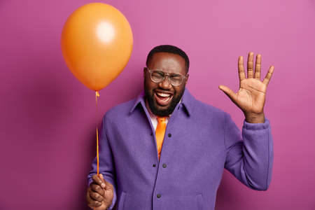 Horizontal shot of glad unshaven man dances carefree, keeps palm raised, laughs positively, holds balloon, happy to be on disco party, isolated over lilac background. Good emotions and feelings