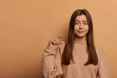 Studio shot of unimpressed beautiful woman makes little size gesture, demonstrates tiny object, wears loose sweatshirt, isolated over brown wall with copy space. Body language, hand sign concept