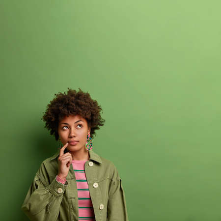 Vertical shot of curly haired young woman with thoughtful expression, keeps finger near lips, dressed in fashionable jacket, poses against green background, copy space for your advertisement