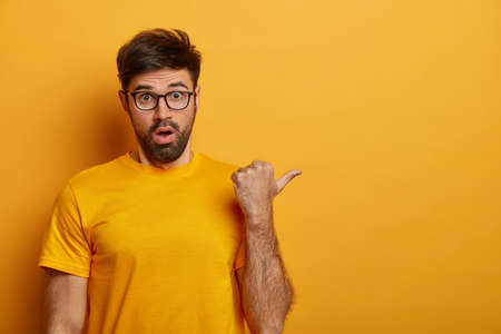 Astonished shocked man spot something terrible aside, notices disturbing astounding thing, stands speechless, wears optical glasses, isolated on yellow background, complains on high prices in store