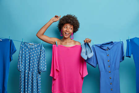 Photo of pleased curly haired woman dances with hand raised, chooses clothes for holiday, corporative party or birthday, going on concert, poses naked behind hanging dress, holds blue footwear Banco de Imagens