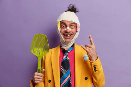 Glad emotive guy makes rock n roll gesture, foolishes around at kitchen, feels energetic, has various shiners, head contusion and missing teeth after crashed by car, poses indoor. People, injuries