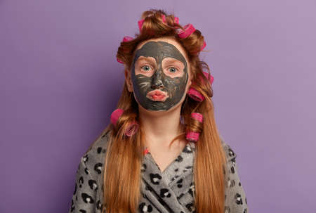 Charming redhead girl lady keeps lips folded, applies clay mask for healthy skin, cares about complexion, wears hair curlers, prepares for important event, wants to look always beautiful and young Stockfoto