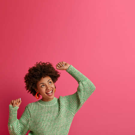 Vertical shot of carefree optimistic woman raises hands up delighted, feels very happy, looks with dreamy expression upwards, feels freedom during leisure time, dances to music triumphs over something