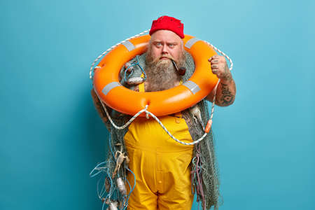 Angry irritaed sailor clenches fist, poses with inflated ring, wears red hat and yellow overalls, busy fishing, isolated on blue background. Experienced fisherman or seaman carries swim ring.