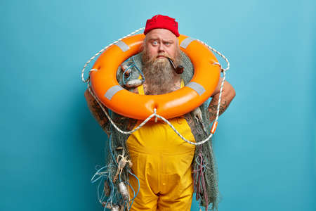 Experienced sailor carries inflated swim ring and smoking pipe, busy with vessel mainetnance, enjoys fishing on boat, stands watch, isolated over blue background. Sea voyage, traveling concept Imagens