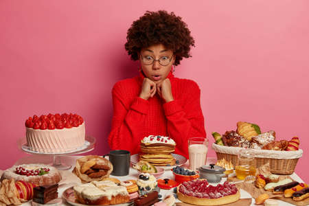 Photo of shocked female sweet tooth looks at table with various desserts, stares at creamy pancakes, wears big round glasses and red sweater, amazed with eaten so much calories, isolated on pink