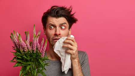 Photo of displeased allergic man reacts surprisingly at allergen, holds handkerchief near runny nose, has swelling around eyes, suffers from pollen allergy, stands indoor against pink background