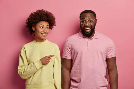 Positive curly haired woman points at funny black guy, stand shoulder to shoulder against pink background, have fun together, suggests ask him for help. Afro American couple gesture and smile indoor