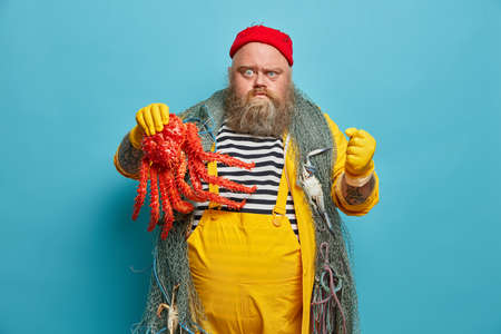 Photo of irritated fisherman holds octopus, clenches fist angrily, being angry with someone, wears red hat, striped sailor jumper and overalls, poses against blue background, works on sailing boat