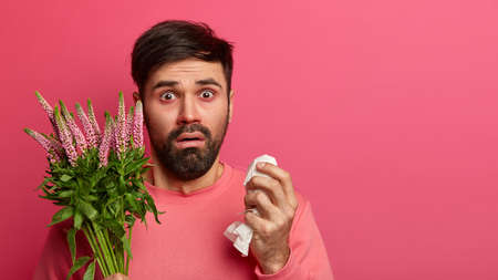 Photo of bearded man suffers from seasonal allergy, has itchy eyes and runny nose, holds napkin for blowing nose, allergic to flowering plant, treats sickness, has unhealthy look, cannot breath free