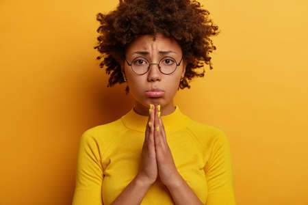 Photo of hopeful displeased Afro American woman makes cute eyes, sobbing expression, says please, wants something badly, presses palms together, asks for favor, pleads apology, wears round spectacles Фото со стока