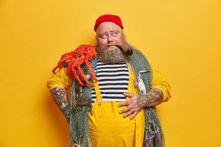 Pensive tattooed sailor keeps hand on belly, carries fishing net over neck, octopus on shoulder, satisfied with successful fishing, takes break, smokes pipe, concentrated with thoughtful expression