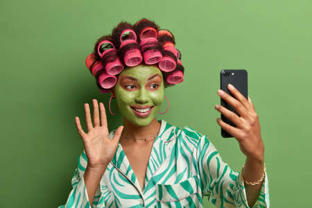 Glad female model with green facial mask, waves palm and says hello to friend, has video conference via modern smart phone, wears hair curlers for making perfect haircut, dressed in casual clothing
