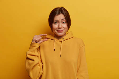 Pretty young European woman shows small size, demonstrates tiny measure, speaks about amount, dressed inn casual hoodie, shapes little object, isolated on yellow background. Body language concept.
