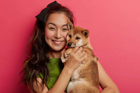 Adorable cheerful young Asian woman embraces pet, feels happy to get popular Japanese pedigree dog, being friendly companion of owner. Pretty girl likes animals, plays with favourite pet indoor