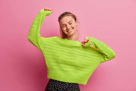 Carefree energized young woman feels optimistic and glad, raises hands and feels pleased, keeps eyes closed, dressed in knitted green sweater, enjoys perfect day off, triumphs over something