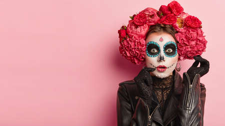 Studio shot of lovely woman wears halloween makeup, dressed in black outfit, red wreath, has zombie image, looks with scaring expression, isolated over rosy background, free space for your promotion