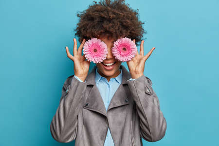 Curly haired positive woman keeps pink gerbera daisy in front of eyes, hides face and smiles broadly. Positive Afro American lady poses with flowers against blue wall. Female gardener indoor