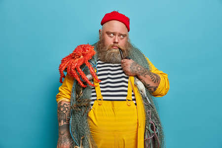 Image of thoughtful man has marine occupation, smokes pipe with pensive sad expression, poses with fishing equipment, carries octopus, thinks about next sea voyage or adventure, isolated on blue wall