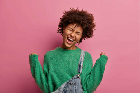 Extremely joyful dark skinned woman raises clenched fists, exclaims from happiness, feels lucky to win something, celebrates amazing victory, closes eyes and smiles broadly, isolated on pink wall