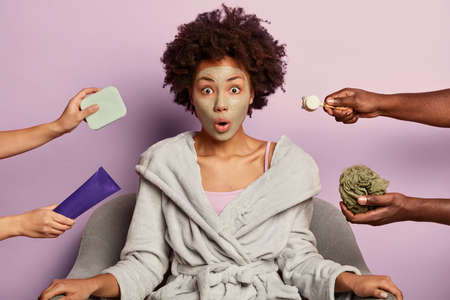 Young surprised woman takes care of her skin, cleans pores with facial mud mask, wears domestic bathrobe, looks with omg expression, sits at armchair against purple background, gets beauty treatments