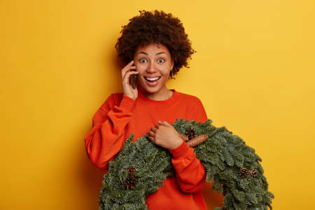 Merry winter holidays concept. Happy dark skinned woman gets congratulations via cell phone, has good mood during telephone conversation holds festive xmas wreath with pine cones. New Year decorations