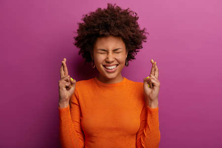 Hopeful wishful dark skinned woman crosses fingers for having luck, prays all okay, smiles happily, makes wish, wears orange turtleneck, awaits for miracle, stands indoor against purple background Banque d'images
