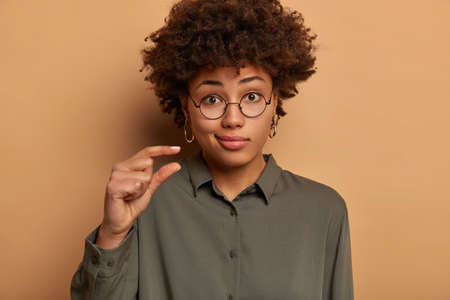 Puzzled displeased dark skinned woman shapes item with small size, confused by something very little, smirks face, wears optical glasses and shirt, explains and measures with fingers, stands indoor