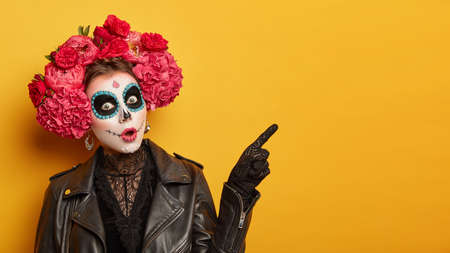 Shocked female wears creative sugar skull makeup, wreath made of red peonies, celebrates All Souls day, holiday in Mexico points away with index finger isolated over yellow background shows copy space