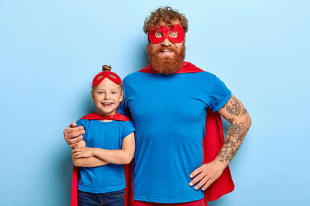 Family portrait of funny father and daughter play superhero, pretend being superpowerful, cuddle indoor, wears special costumes with mask and cape, isolated on blue background. Children holiday
