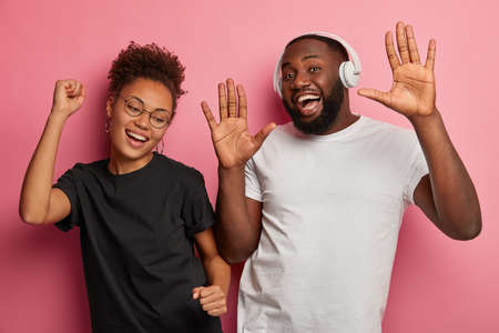 Staying alive and having fun together. Happy dark skinned millennial girlfriend and boyfriend feel relaxed, dance and listen songs in headphones, isolated over pink wall, clench fists and raise palms