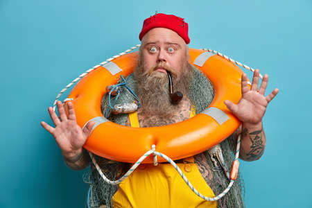 Scared seaman raises palm, stares bugged eyes, afraids of smimming, poses with orange inflated lifebuoy, fishing net, being seasick, isolated on blue background. Fearful member of deck department