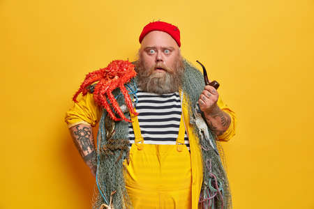 Skilled male mariner has stupefied expression, stares at camera and smokes pipe. Fat bearded professional fisherman poses with octopus on shoulder, scared of something terrible happening at sea