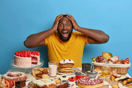 Emotive dark skinned bearded guy keeps both hands on head, opens mouth from surprisement as sees too much desserts at one table, shocked his wife baked lots of confectionery for festive event