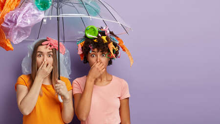 Fie, what nasty smell. Disgusting two women cover noses, hold polythene umbrella, collect plastic wastes, isolated on purple background with blank space. Volunteers clean nature from garbage Banco de Imagens