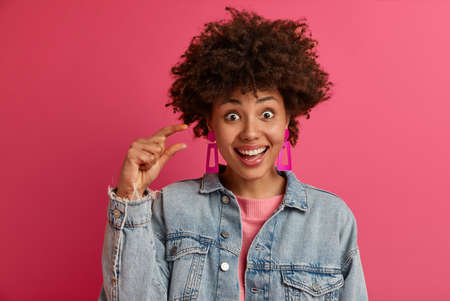 Photo of happy smiling woman shows small amount of something, shapes tiny size of something, has upbeat mood, measures little invisible object, wears denim clothes, models and gestures indoor